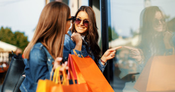 Two young women in shopping looking at shop window in the city