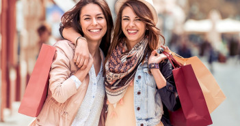 Shopping and tourism concept- beautiful girls with shopping bags in ctiy